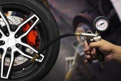 Вручите держать калибровочные инструменты inflator, колеса сплава гоночного автомобиля Стоковое Фото