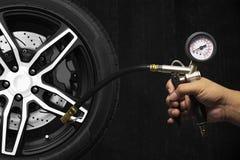 Вручите держать калибровочные инструменты inflator, колесо сплава гоночного автомобиля Стоковые Фотографии RF