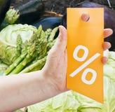 Вручите держать карточку для рабатов против продуктов Стоковые Фотографии RF