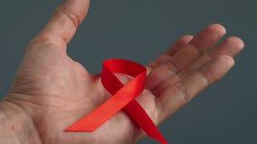 Вручите держать красный символ ленты осведомленности СПИДА ВИЧ сток-видео