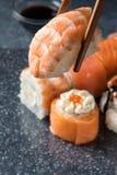 Вручите держать суши палочек с креветкой на предпосылке серого цвета Стоковая Фотография