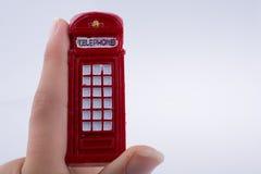 Вручите держать телефонную будку на белой предпосылке Стоковые Фотографии RF