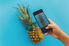 Вручите держать телефон и принимать фото ананаса в спетом стильном Стоковые Фотографии RF