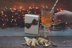Вручите держать чашку чаю, fairy света рождества, подарочную коробку Стоковая Фотография