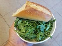 Вручите держать шар зеленых цветов arugula и хлеб над плиточным полом Стоковые Фото