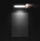 Вручите держать лампу около стены с пустым модель-макетом плаката Стоковое фото RF