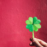 Вручите держать бумажный shamrock зеленого цвета origami на пинке Стоковые Изображения