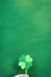 Вручите держать бумажный shamrock зеленого цвета origami на предпосылке стены Стоковое Фото