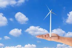 Вручите держать ветротурбины производя электричество на голубом небе стоковые фотографии rf