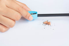 Вручите держать голубую точилку для карандашей с shavings на белом backgr Стоковая Фотография