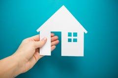Вручите держать диаграмму дома белой бумаги на голубой предпосылке имущество принципиальной схемы реальное строить экологический  Стоковые Фотографии RF