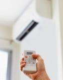 Вручите держать дистанционное управление, регулируя температуру кондиционера воздуха установленную на белой стене Температура ком стоковые фото