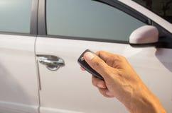 Вручите держать ключ автомобиля с предпосылкой автомобиля нерезкости Стоковая Фотография