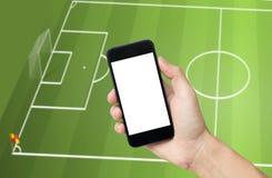Вручите держать мобильный телефон, игру в реальном маштабе времени евро футбола взгляда на черни Стоковые Фотографии RF