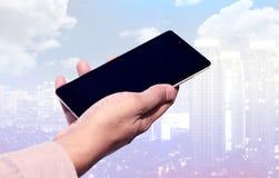 Вручите держать мобильный телефон с пустым экраном на предпосылке городского пейзажа Стоковое Изображение