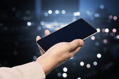 Вручите держать мобильный телефон с пустым экраном на расплывчатом городе ночи Стоковое Фото
