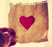 Вручите держать покрашенное бумажное сердце до солнца во время солнец Стоковые Фотографии RF