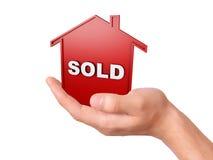 Вручите держать проданный дом изолированный на белой предпосылке Стоковое Фото