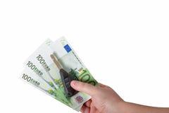 Вручите держать счеты евро и ключи автомобиля изолированными Стоковые Изображения
