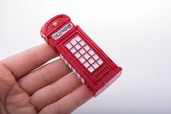 Вручите держать телефонную будку на белой предпосылке Стоковое Изображение