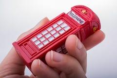 Вручите держать телефонную будку на белой предпосылке Стоковое Изображение RF