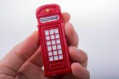 Вручите держать телефонную будку на белой предпосылке Стоковое Фото