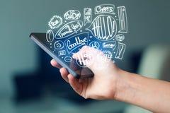 Вручите держать телефон с нарисованными рукой пузырями речи Стоковые Изображения