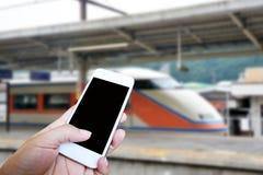 Вручите держать умный телефон над предпосылкой вокзала нерезкости Стоковое фото RF