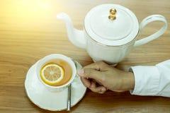 Вручите держать чашку чая с лимоном и чайником куска на деревянном столе Стоковая Фотография RF