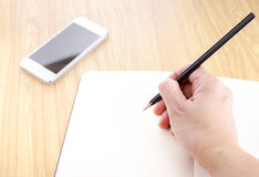 Вручите держать черный карандаш и запись на острословии тетради пробела открытом Стоковое фото RF