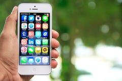 Вручите держать iPhone с социальными применениями средств массовой информации на экране стоковые фото