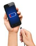Вручите держать smartphone и соедините заряжатель изолированный на белизне Стоковое Фото