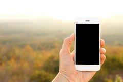 Вручите держать smartphone модель-макета с backgr солнечного света и горы стоковое изображение rf