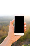 Вручите держать smartphone модель-макета с backgr солнечного света и горы стоковые изображения rf