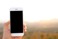 Вручите держать smartphone модель-макета с backgr солнечного света и горы стоковое фото rf
