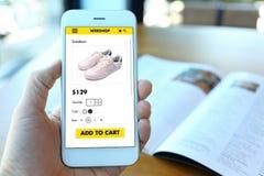 Вручите держать smartphone с выберите ботинки на вебсайте ecommerce стоковая фотография