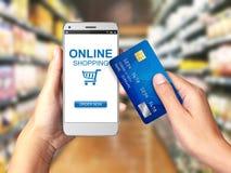 Вручите держать Smartphone с онлайн покупками на дисплее, онлайн концепции покупок стоковая фотография