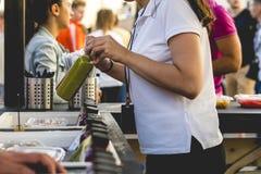 Вручите женщину продавая бутылку свежего сока в внешнем магазине на летний день стоковая фотография