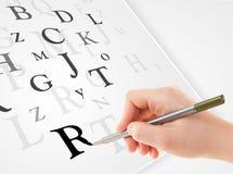 Вручите запись различных писем на белой чистой бумаге Стоковая Фотография RF