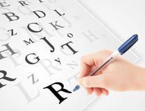 Вручите запись различных писем на белой чистой бумаге Стоковое Изображение