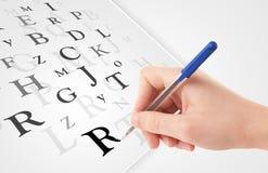 Вручите запись различных писем на белой чистой бумаге Стоковые Фото