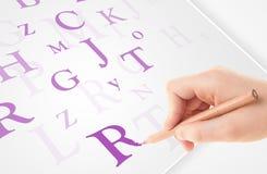 Вручите запись различных писем на белой чистой бумаге Стоковые Изображения