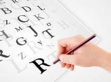 Вручите запись различных писем на белой чистой бумаге Стоковое Изображение RF