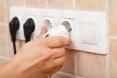Вручите затыкать шнур питания в электрическое приспособление стены стоковое фото rf