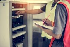 Вручите инженера сети в комнате сервера с ручкой и таблеткой Стоковые Фото