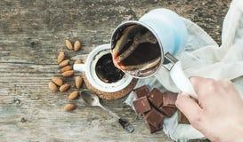 Вручите лить свеже заваренный кофе от cezve - бака кофе - к Стоковое фото RF