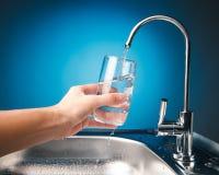Вручите лить стекло воды от крана фильтра стоковая фотография