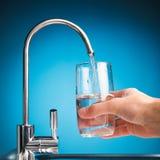 Вручите лить стекло воды от крана фильтра стоковая фотография rf