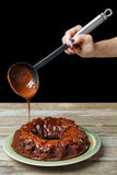 Вручите лить шоколад от ковша на пирожном на зеленой плите на деревянном столе Стоковое фото RF