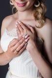 Вручите красивую невесту девушки в белом платье свадьбы с акриловыми ногтями и чувствительными картиной и стразами Стоковое Изображение RF